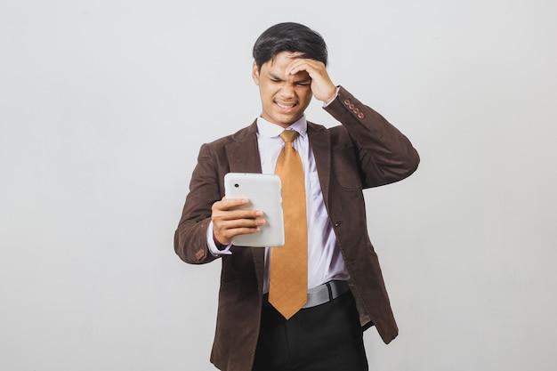 Разочарованный азиатский бизнесмен в костюме и галстуке получил плохие новости со смартфона