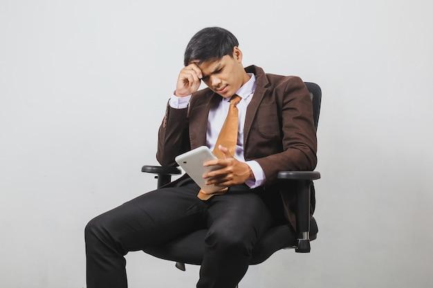 양복 재킷과 넥타이를 입은 실망한 아시아 사업가가 앉아서 스마트폰으로 나쁜 소식을 듣고 있다