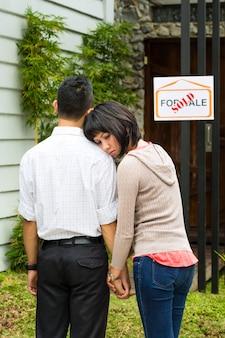 Разочарованная азиатская пара перед домом