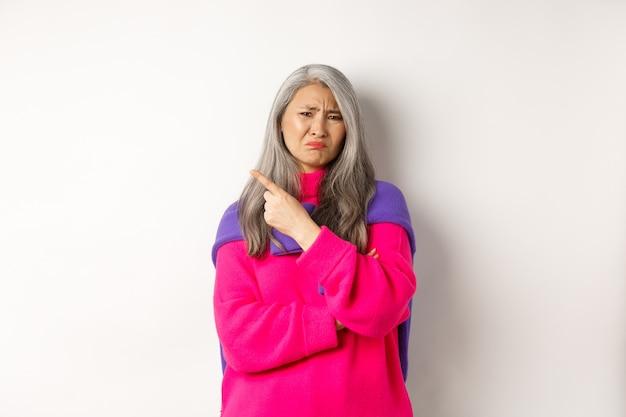 실망한 아시아 할머니는 역겨운 얼굴을 하고 손가락을 왼쪽으로 가리키며 나쁜 것에 대해 불평하며 흰색 배경 위에 서 있다