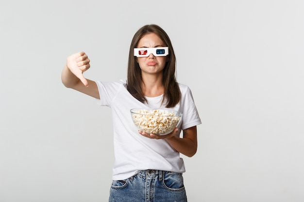 Disappointed attractive girl in 3d glasses, holding popcorn and showing thumbs-down, dislike movie.