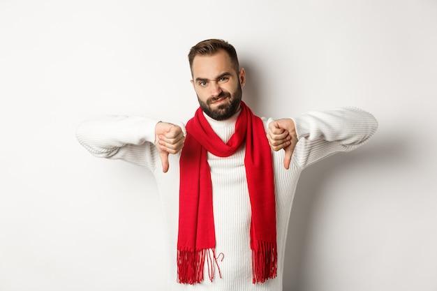 冬のセーターとスカーフで失望したひげを生やした男、親指を下に向けて顔をゆがめ、何かを嫌い、悪い製品を判断し、白い背景の上に立っている