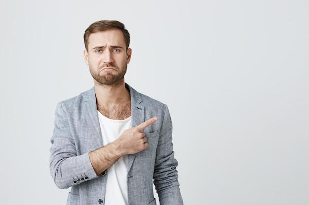 失望したひげを生やした男が指を右に向けて不平を言う