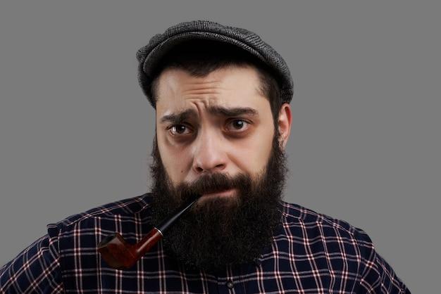 パイプを吸っているがっかりしたひげを生やした男は、市松模様のシャツを着てカメラを見てください。人は仕事を失った。疲れた労働者は、生活水準を向上させる方法についてアドバイスを待ちます。男性の顔に後悔の感情。