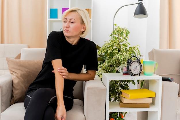실망 된 아름 다운 금발 러시아 여자 팔을 잡고 측면을 찾고 안락의 자에 앉아