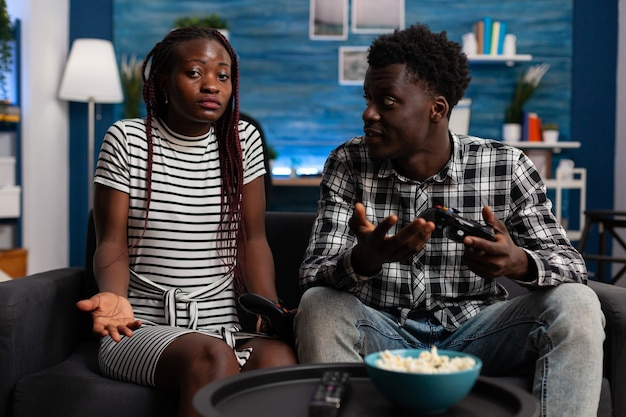 Разочарованная черная пара проигрывает в видеоигре по телевизору