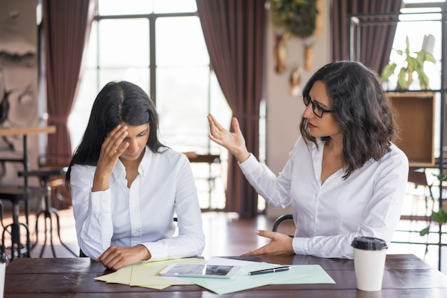 Disappointed business woman scolding colleague.