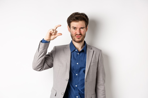 Разочарованный бизнесмен, показывающий небольшой размер и гримасничающее расстройство, небольшой доход, недовольный стоя на белом фоне.