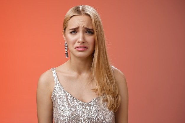 Disappointed complaining cute blond woman in silver stylish dress grimacing frowning upset have bad day pouting pity standing displeased unhappy heartbroken everything bad, red background.