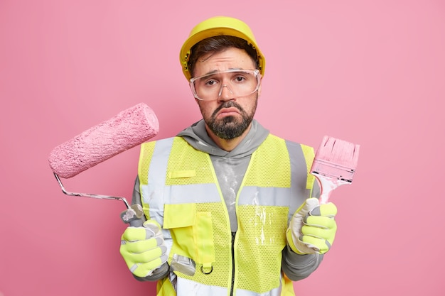 Disappointed construction worker holds painting roller and brush restores paints walls of building wears protective helmet uniform and safety glasses