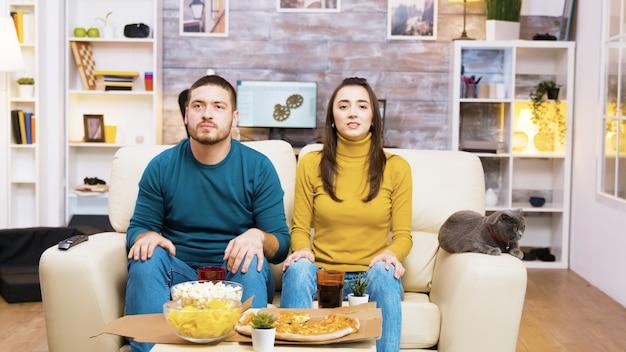 お気に入りのサッカーチームが試合に負けた後、失望したカップル。ソファに横になっている猫。コーヒーテーブルの上のポップコーン、ピザ、ソーダ。