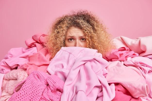 ピンクの壁に散らかった服のポーズで覆われた失望した巻き毛の女性は、カメラを悲しそうに見ています