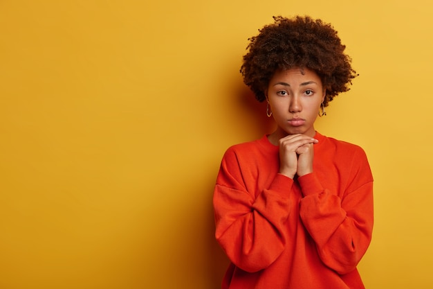 Disappointed curly young woman keeps hands under chin, looks sadly at camera, feels loneliness, dressed in jumper