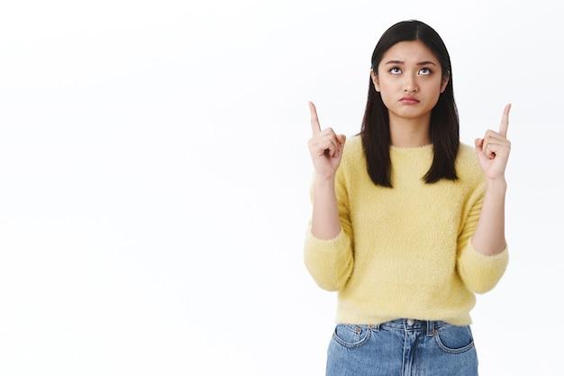 위를 쳐다보고 회의적이고 음산한 실망한 귀여운 우울한 소녀. 노란색 스웨터를 입은 아름다운 아시아 세련된 여성이 위로 가리키며 후회하며 좋은 기회를 놓치고 흰 벽