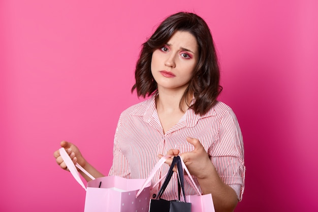 Disappointed dark haired woman, wears rose blouse, holds opened bag. beautiful brunette looks unhappy, dislikes purchase.