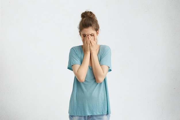 Разочарованная удрученная женщина с пучком волос в голубой футболке, закрывающей лицо руками, уставшими и измученными. отчаявшаяся женщина в депрессии, пряча плачущее лицо руками