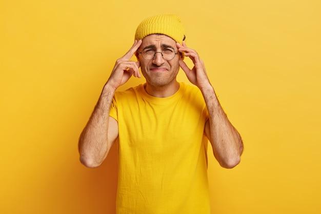 がっかりした不機嫌な男は、頭に手を置き、顔を笑い、頭痛に苦しみ、表情に不満を持っています
