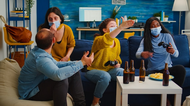 Disappointed diverse people loosing playing video games at home respecting social distancing because of corona outbreak wearing face mask against spreading virus. new normal party social distance
