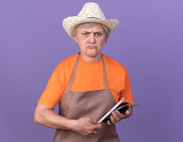 紫色の巻尺でナスを測定する園芸帽子をかぶっている失望した年配の女性の庭師