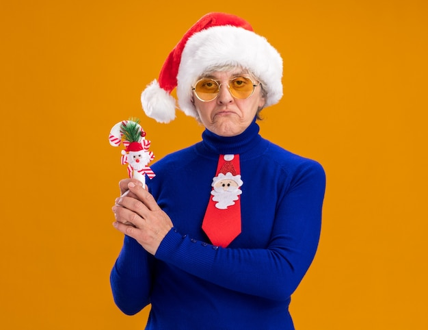 Disappointed elderly woman in sun glasses with santa hat and santa tie holding candy cane isolated on orange wall with copy space