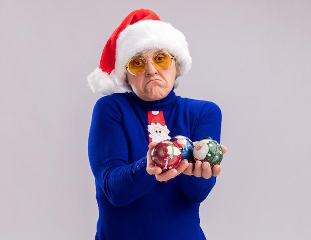 Donna anziana delusa in occhiali da sole con cappello santa e cravatta santa tenendo gli ornamenti di palla di vetro