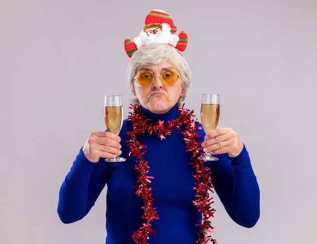Disappointed elderly woman in sun glasses with santa headband and garland around neck holds glasses of champagne isolated on white wall with copy space