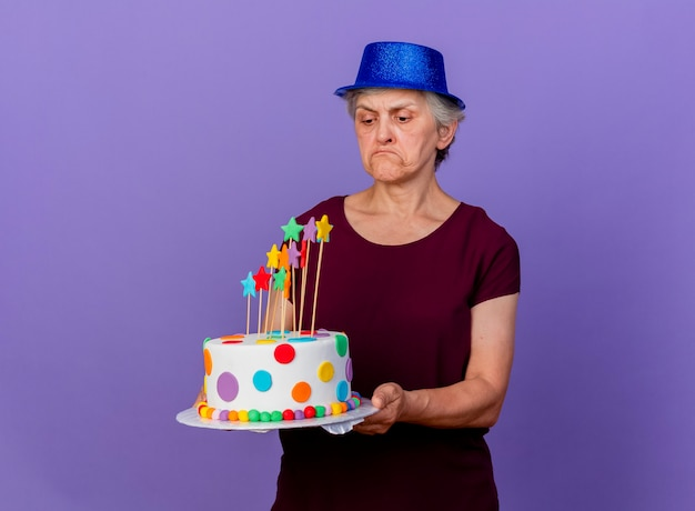 Disappointed elderly woman wearing party hat holds and looks at birthday cake isolated on purple wall with copy space