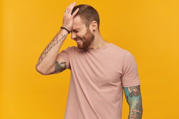 Disappointed embarrassed young bearded man with tattoo and eyes closed in pink tshirt keeps hand on forehead and looks upset over yellow wall