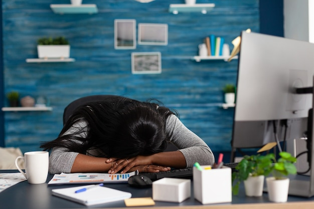 Disappointed exhausted black student sleeping on desk table in living room overworking remote from home