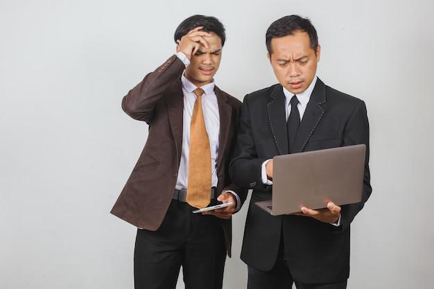 노트북에서 나쁜 소식을 들은 두 아시아 사업가의 실망한 표정