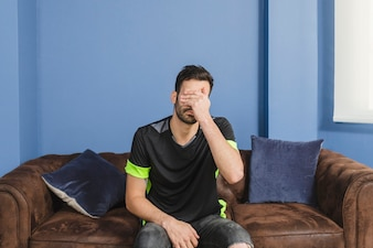 Disappointed football fan on couch