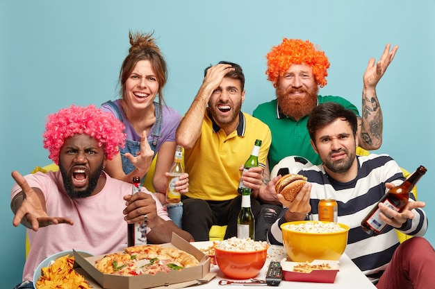 Quattro uomini e una donna delusi guardano una partita sportiva, insoddisfatti del fallimento della squadra, bevono birra, fanno uno spuntino, esprimono reazioni negative, emozioni negative, posano insieme sul divano di casa. la squadra perde.