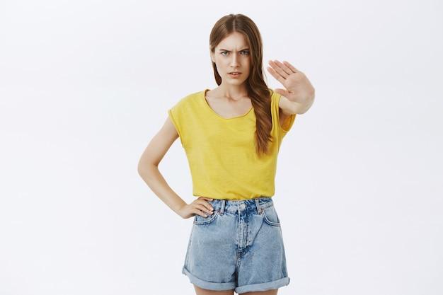 Разочарованная хмурящаяся девушка показывает жест стоп, запрещает или отказывается что-то всепоглощающее