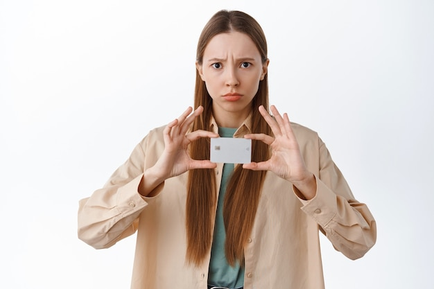 Disappointed frowning girl sulking, complaining on bank, showing credit card with displeased unfair face, being jealous, standing over white wall