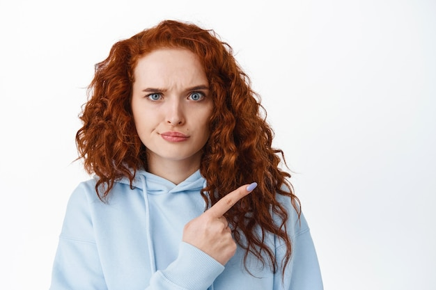 Disappointed frowning redhead woman pointing finger right at something bad, scolding or complaining, look upset and dissatisfied, white wall