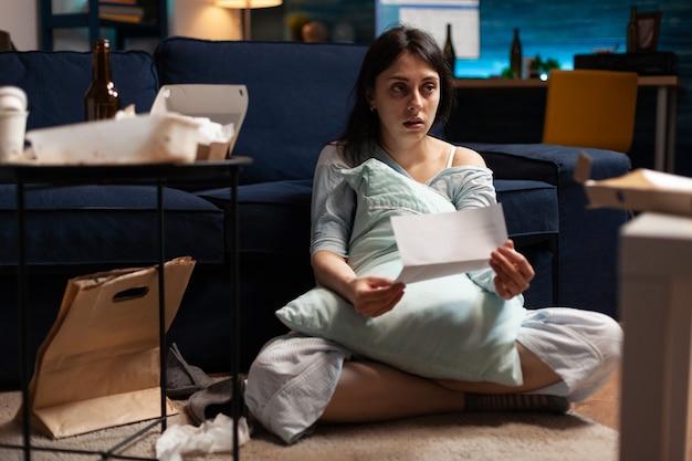 Разочарованная разочарованная депрессивная отчаянная женщина сидит на полу