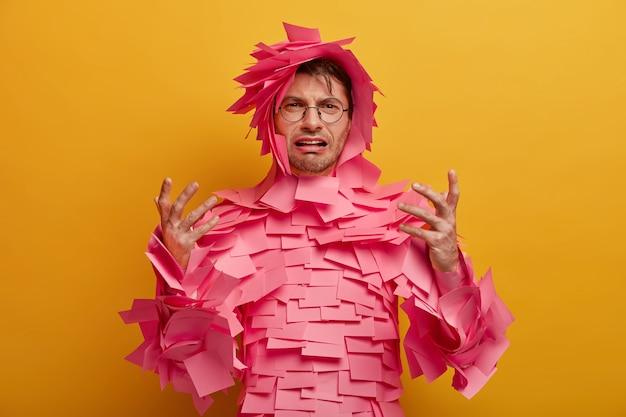 失望した欲求不満の男のジェスチャーと不幸に見え、ピンクの付箋紙で覆われ、絶望からの叫び、黄色の壁に隔離された悪いニュースを見つけます。否定的な感情