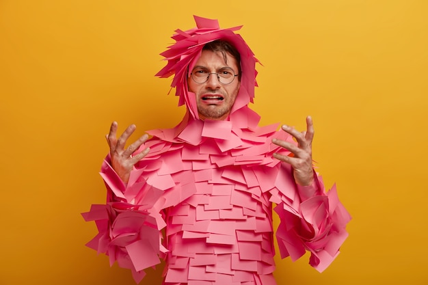 Disappointed frustrated man gestures and looks unhappily , finds out bad news, covered with pink sticky notes, cries from despair, isolated over yellow wall. negative emotions