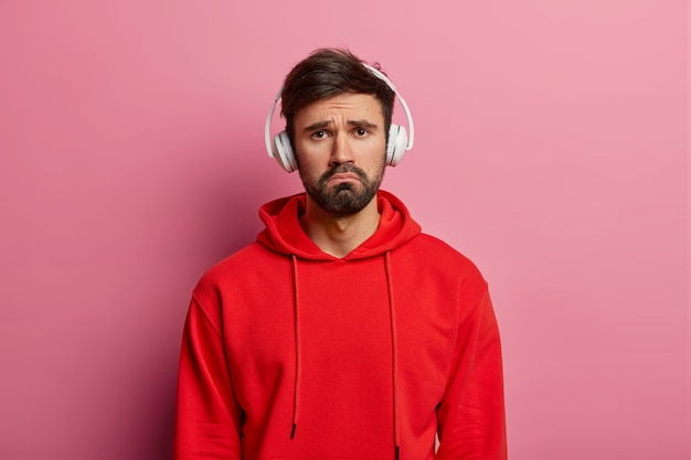 Disappointed frustrated unhappy man tries to entertain himself with music, has melancholic face expression, wears headphones on ears, dressed in red hoodie, isolated over rosy pastel wall.