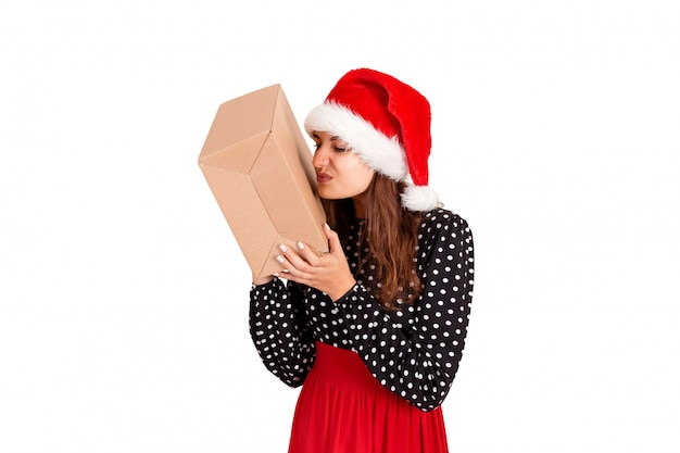 Disappointed girl in christmas hat holding a big gift in her hand. isolated on white . holidays