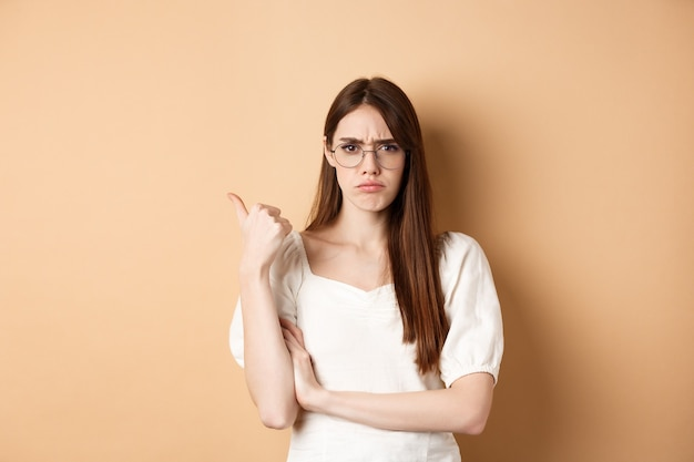 Disappointed girl in glasses frowning, pointing aside at bad product, disapprove and dislike something, standing on beige.