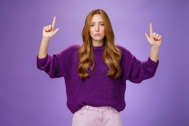 Delusa, cupa e lunatica, attraente donna dai capelli rossi con le lentiggini in un maglione caldo che alza le mani p...
