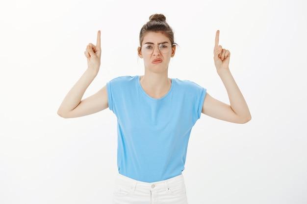 Donna delusa e cupa che si lamenta di qualcosa, puntando le dita verso l'alto con la faccia scontenta