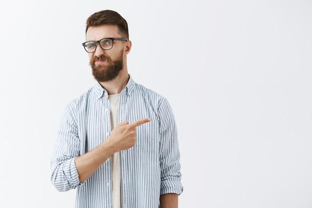 Разочарованный бородатый мужчина с гримасой позирует у белой стены