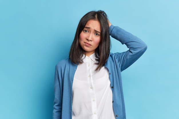 Disappointed grumpy brunette young woman with eastern appearance scratches head frowns face looks unhappily at camera wears white shirt and blue jumper poses indoor. negative emotions concept