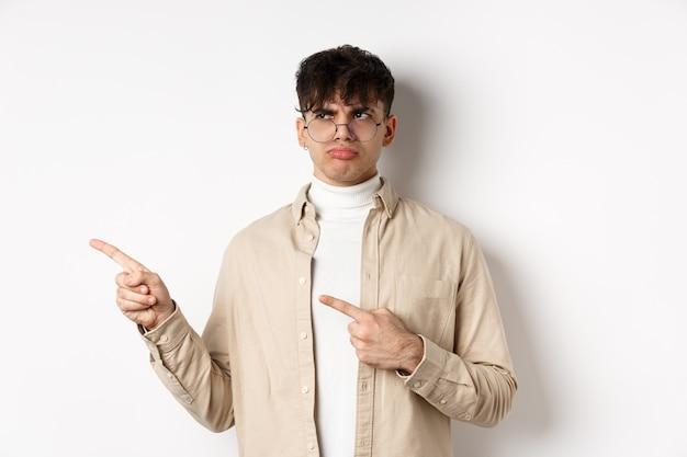 眼鏡をかけた失望した男が左を向いて、不機嫌になり、悪い申し出に不平を言い、白い背景に動揺して立っている
