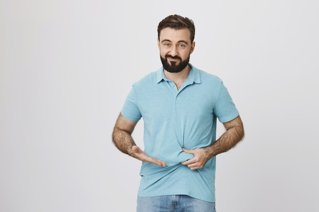Disappointed guy need lose weight, showing fat belly