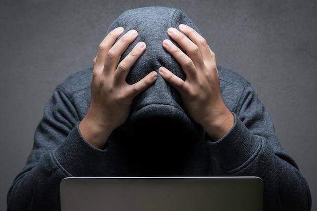 Разочарованный хакер с компьютерным ноутбуком