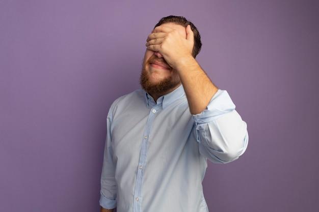 L'uomo biondo bello deluso mette la mano sulla faccia isolata sulla parete viola