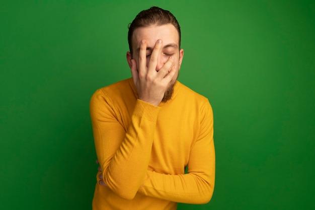 실망 된 잘 생긴 금발 남자는 녹색에 얼굴에 손을 넣습니다